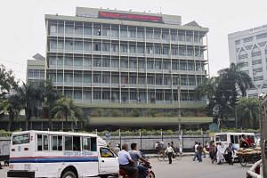 Commuters pass by the front of the Bangladesh central bank building in Dhaka.