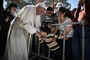 The Pope being greeted by a child during his visit to the Moria detention centre for migrants and refugees on Lesbos island in Greece on Saturday. That day, he took 12 Syrians from three families - all Muslims - home with him to the Vatican.