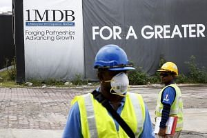 Construction workers stand in front of a 1Malaysia Development Berhad (1MDB) billboard at the Tun Razak Exchange development in Kuala Lumpur.