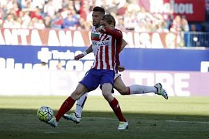 Atletico Madrid's Fernando Torres (front) scores a goal past Granada's Cristiano Biraghi on Sunday.