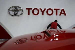 An employee working under a Toyota Motor Corp logo at the company's showroom in Tokyo, Japan on Feb 5, 2016.