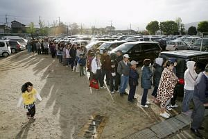 People line up to get food and water supplies at an elementary school acting as an evacuation center, on April 17, 2016.