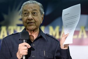 Former Malaysian prime minister Mahathir Mohamad shows a citizens' declaration documents during a press conference.