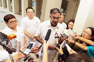 Lawyer Murali Pillai, the PAP's candidate for the by-election, speaking to reporters yesterday after house visits in Bukit Batok SMC. Among residents' top concerns is adequate help in the economic slowdown, he said.
