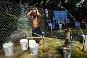 Mr Charlie Wong rinsing himself at the Sembawang hot spring to keep cool on June 24, 2012.
