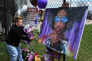 Prince fan Darcie Ludeman attaching flowers to a memorial wall outside the Paisley Park residential compound in Minneapolis, Minnesota, on April 22, 2016.