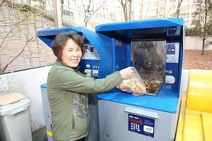 South Korean housewife Cho Sung Ja using an RFID food waste disposal system that is able to weigh how much trash each household generates and bill it accordingly. She lives in a three-bedroom apartment with her husband and son in Mapo, a mid-sized di
