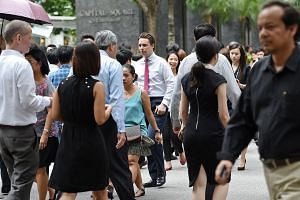 Office workers at a pedestrian crossing along Church Street at Raffles Place.