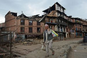 A Nepalese man walking amidst the rubble of collapsed houses after an earthquake in Bhaktapur, on April 27, 2015.