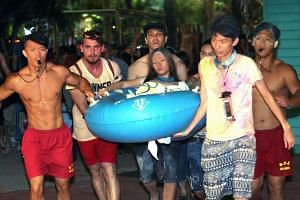 Life guards carrying a young woman suffering from facial burns to an ambulance in the aftermath of the Taiwan waterpark explosion on June 27, 2015.