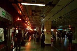 The Tiong Bahru MRT station with its emergency lights on as many passengers waited in the train for service to resume on April 25, 2016.