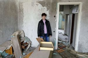 M Zoya Perevozchenko poses for a photograph in her house in the ghost town of Pripyat, Ukraine, on April 5, 2016.