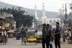 Filipino policemen stand guard on the spot where the head of a hostage was dropped off in Jolo on April 25, 2016.
