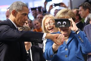 Mr Obama giving Dr Merkel a hand as she tried on a virtual reality device made by German automation company ifm electronic at a trade fair in Hanover yesterday. At the end of a six-day foreign tour, the US leader made an impassioned plea for European