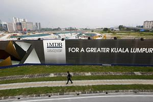 A man walking past a 1MDB billboard at the funds flagship Tun Razak Exchange development in Kuala Lumpur, in this March 1, 2015 file photo.