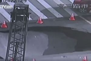 A portion of the road collapsing into the ground, minutes after police officers had fenced off the area with traffic cones.