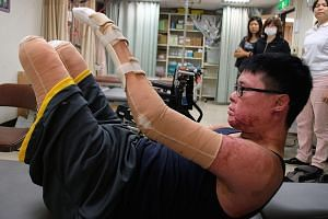 Mr Huang working out at a recovery centre in Taipei. He has decided to rebuild his life and not dwell on the past. Despite his amputations, he insists on doing what used to be simple tasks whenever he can. He eats with a utensil strapped to his bound