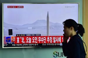 A woman walks past a TV screen showing a file footage of a North Korean missile launch at a railway station in Seoul on April 28, 2016.