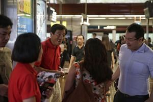 SDP chief Chee Soon Juan (in red shirt) hands out campaign leaflets at Bukit Batok MRT station on April 28, 2016.