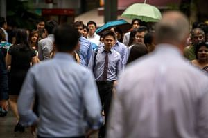 Pedestrians cross a street in the Central Business District of Singapore.