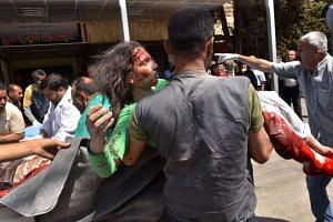 A Syrian civil defence member carries a wounded woman into a hospital in the government-controlled side of Aleppo.