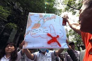 Mr Pan Chung-chiu (right), the owner of a Taiwan fishing boat detained by Japan, painting a red cross on a map over the location of the Okinotori Island during a protest by Taiwan fishermen in front of Japan's representative office in Taipei, Taiwan,