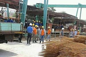 Workers gathering at the site in Tampines Industrial Street 62, where the fatal accident happened on Tuesday morning.