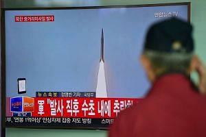A man watches a TV news showing file footage of a North Korean missile launch at a railway station in Seoul, on April 28, 2016.