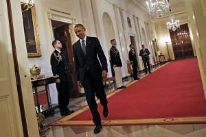 US President Barack Obama walks to a ceremony at the White House.