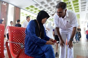 PAP candidate Murali Pillai speaking to a resident during a walkabout inside the Bukit Batok bus interchange on May 1, 2016.