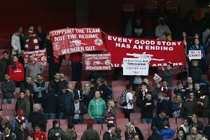 Arsenal fans protest with signs at the end of the match.