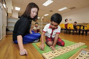 Senior teacher Pauline Yong guiding an N2 pupil at Brighton Montessori as he uses the Seguin board to learn about the ones and tens of two-digit numbers. The children move from doing something concrete with counting beads to the abstract of recognisi