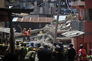 Rescuers search for bodies trapped in rubble on May 2, 2016 at the scene of a collapsed residential building in the low-income suburb of Huruma in Nairobi.