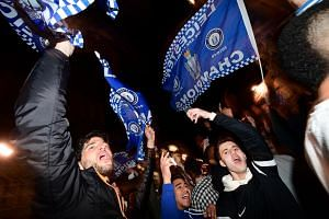 Leicester City fans wave flags as they celebrate their team becoming the English Premier League champions in central Leicester.