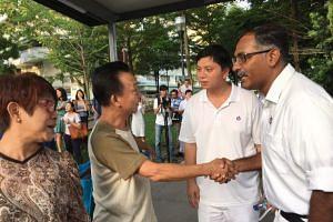 PAP's Murali Pillai shaking a resident's hand at Bukit Batok Central.