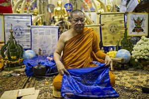 Thai Buddhist monk Phra Prommangkalachan displays a sacred Leicester City fabric and talisman at Wat Traimit temple in Bangkok, Thailand, on May 2, 2016.