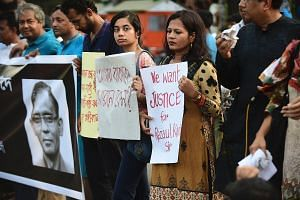 Protesters and former Rajshahi University students holding placards during a demonstration in Dhaka last Friday against the killing of English professor Rezaul Karim Siddique.