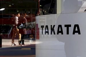 A logo of Takata Corp is seen with its display as people are reflected in a window at a showroom for vehicles in Tokyo.