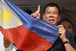 "Philippine Presidential candidate Rodrigo ""Digong"" Duterte holds the national flag during an election campaign in Malabon, Metro Manila on April 27, 2016."