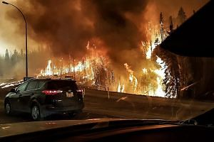 A picture provided by Twitter user @jeromegarot yesterday shows a wildfire raging through Fort McMurray on Tuesday.