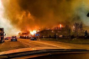 A picture provided by Twitter user @jeromegarot on May 5, 2016, shows a wildfire raging through the town of Fort McMurray, Canada.
