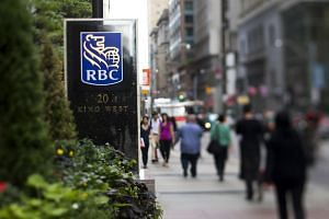 Pedestrians pass in front of the RBC Royal Bank sign outside the company's office near Bay Street, Toronto.
