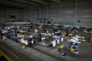 Fort McMurray wildfire evacuees lie on cots at a hockey rink in Lac La Biche, Alberta, Canada, on May 5, 2016.
