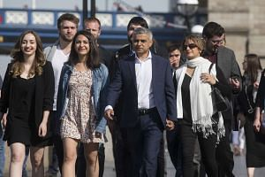 Sadiq Khan (centre) arrives with members of his team at City Hall in London, on May 6, 2016.