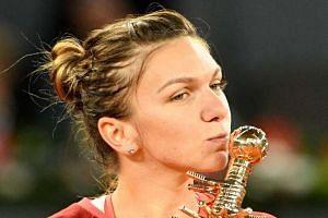 Romania's Simona Halep kisses the trophy after beating Slovakia's Dominika Cibulkova.