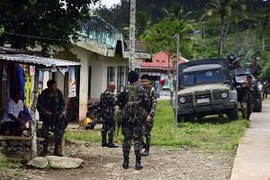 Filipino soldiers on patrol in front of a school to be used as a poll precinct in Ormoc, Leyte island, Philippines on May 8, 2016.