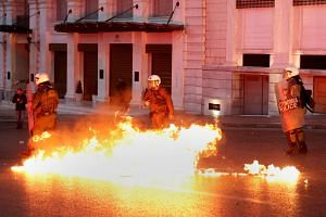 Greek riot police officers dodge a petrol bomb thrown by protesters following a protest outside parliament in Athens.