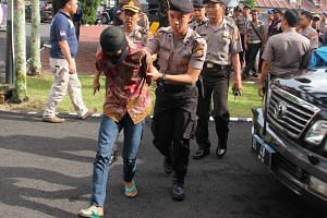 An Indonesian policemen bringing one of the underaged suspects in the gang rape and murder of a 14-year old girl, on May 5, 2016.