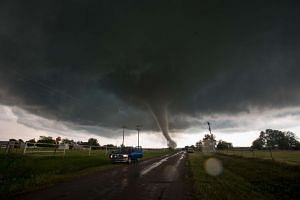 Vehicles stop on the side of a road as a tornado rips through a residential area after touching down south of Wynnewood, Oklahoma, on May 9, 2016.
