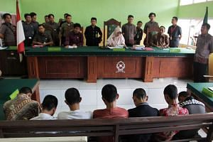 An Indonesian judge (centre) reads the sentence to seven teenage suspects during their trial in Curup, Bengkulu province, on May 10, 2016.